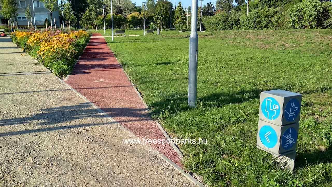 információs táblák és dísznövények a futópálya mentén